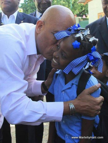 Haiti President Michel Martelly kissing a Haitian school girl