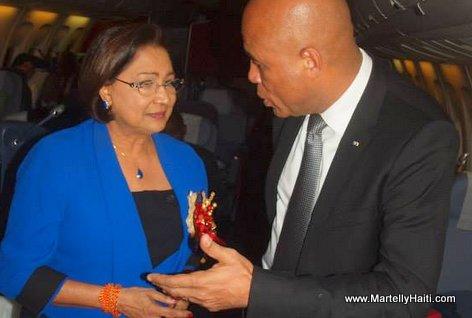Le Chef de l'Etat, en conversation avec le Premier ministre de Trinidad & Tobago, Mme Kamla Persad-Bissessar, dans l'avion vers Johanesburg (Afrique d