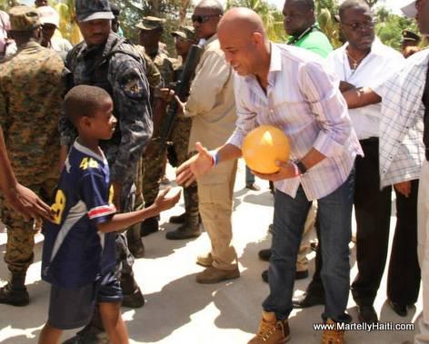President Martelly fe yon timoun kado yon boul pandan inauguration yon pon nan Arcahaie Haiti