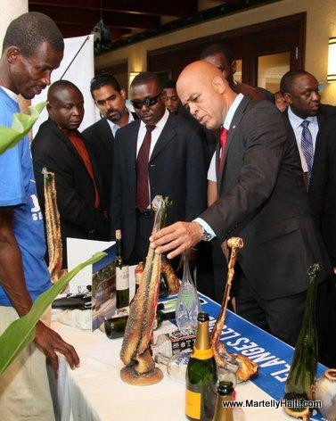 President Michel Martelly contemplant un objet d'art realise par un artisan fait de matieres recyclees