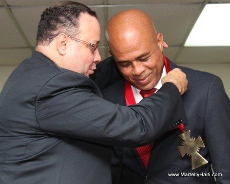 President Michel Martelly recevant la decoration des mains de Gilberto Boutin, Doyen de la faculte de Droit et des Sciences politiques de l'Universite