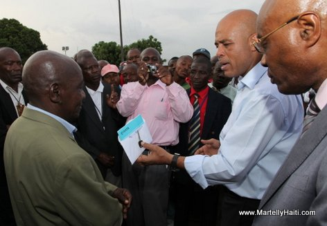 President Michel Martelly remettant la cle d'un autobus de 92,000 dollars americains a l'Association des Red-Caps